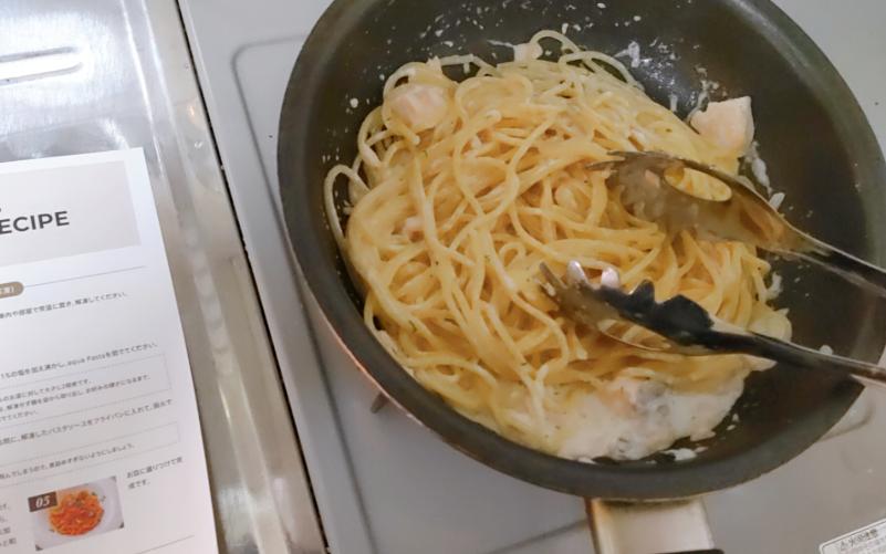フライパンでパスタとソースを混ぜる